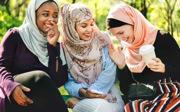 photo of women laughing and dressed in hijabs sitting next to each other