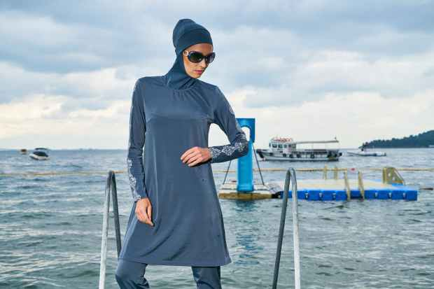 woman in blue hijab and long sleeved dress standing near body of water